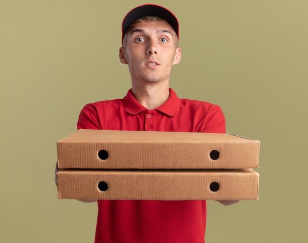 Repartidor rubio joven impresionado sostiene cajas de pizza en verde oliva