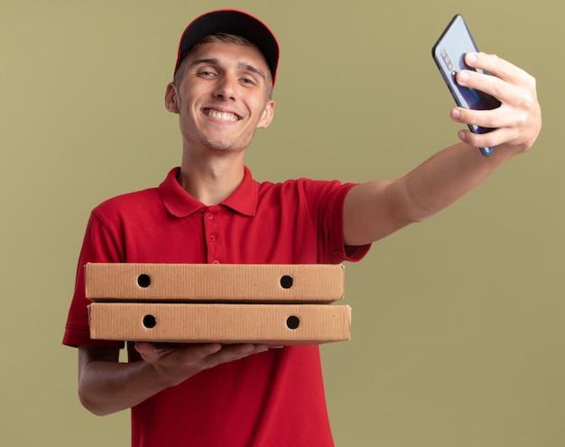 Repartidor rubio joven sonriente sosteniendo cajas de pizza y teléfono