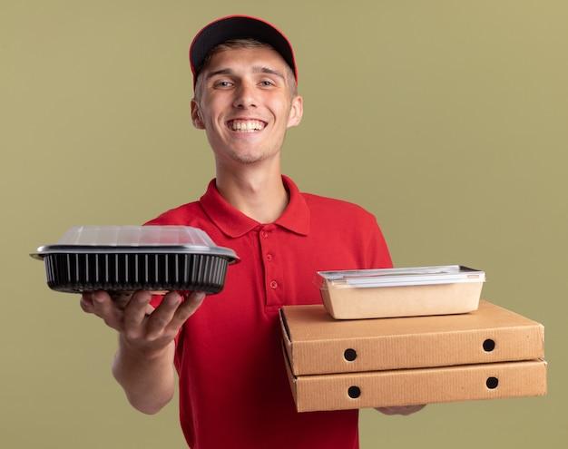 Repartidor rubio joven sonriente sostiene envases de alimentos y paquetes de alimentos en cajas de pizza