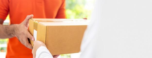 Repartidor de servicio de mensajería dando caja de paquetería al cliente