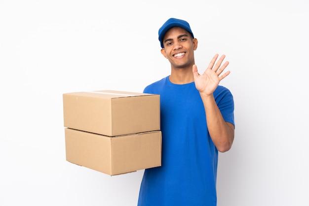 Repartidor sobre pared blanca aislada saludando con la mano con expresión feliz