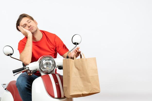 Repartidor soñoliento joven en uniforme rojo sentado en scooter sosteniendo una bolsa de papel en la pared blanca
