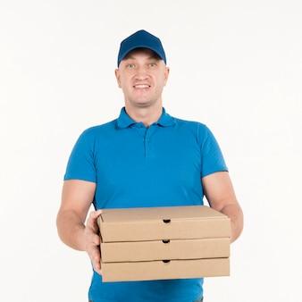 Repartidor sonriendo mientras sostiene cajas de pizza
