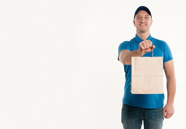 Repartidor sonriente con bolsa de papel con espacio de copia