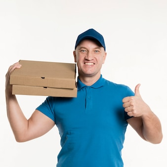 Repartidor sonriente dando pulgares mientras transportaba cajas de pizza