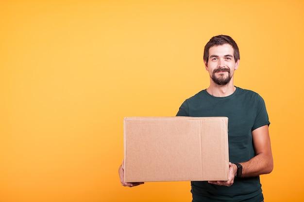 Repartidor sonriente feliz atractivo con una caja de cartón en sus manos sobre fondo amarillo en estudio
