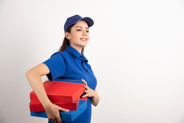 Repartidor sonriente feliz en uniforme azul con cajas de pizza para llevar sobre fondo blanco. foto de alta calidad