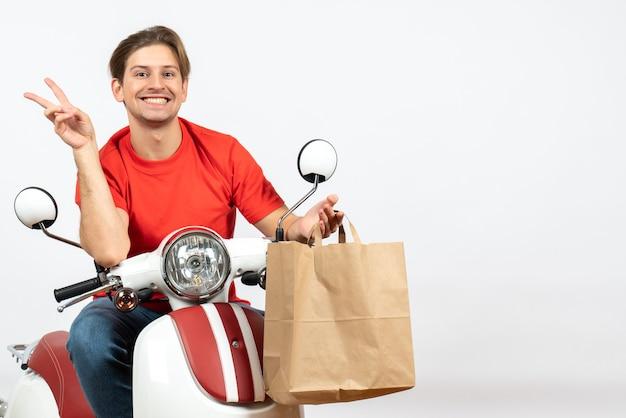 Repartidor sonriente joven en uniforme rojo sentado en scooter sosteniendo una bolsa de papel y haciendo gesto de victoria en la pared blanca