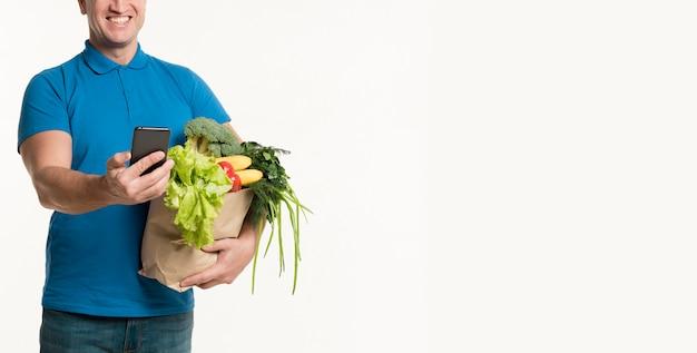 Repartidor sonriente mirando smartphone mientras sostiene una bolsa de supermercado