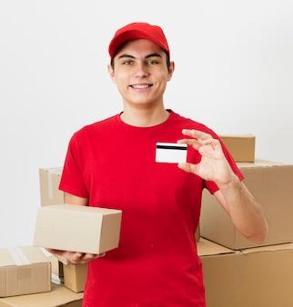 Repartidor sonriente mostrando tarjeta de crédito