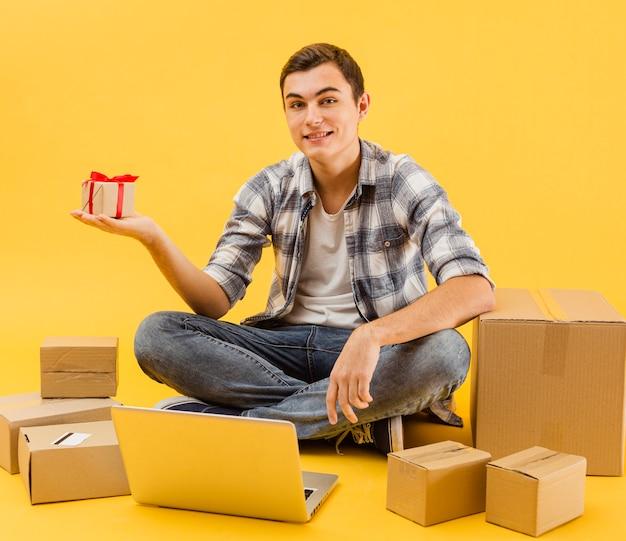 Repartidor sonriente con paquetes al lado