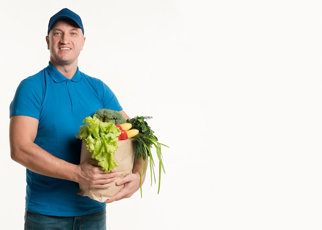 Repartidor sonriente posando con bolsa de supermercado
