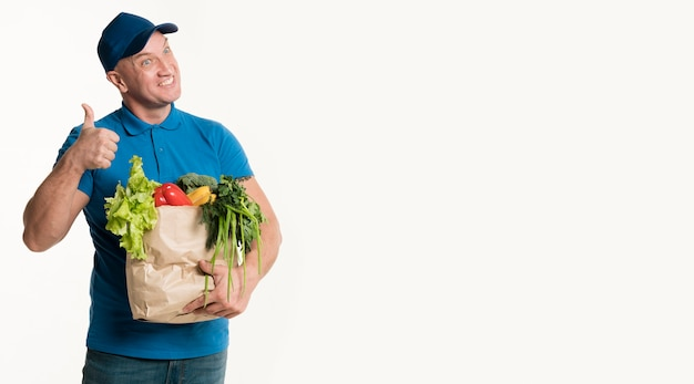 Repartidor sonriente pulgares arriba mientras sostiene la bolsa de supermercado