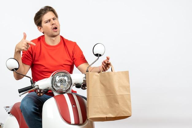 Repartidor sorprendido joven en uniforme rojo sentado en scooter apuntando la bolsa de papel en la pared blanca