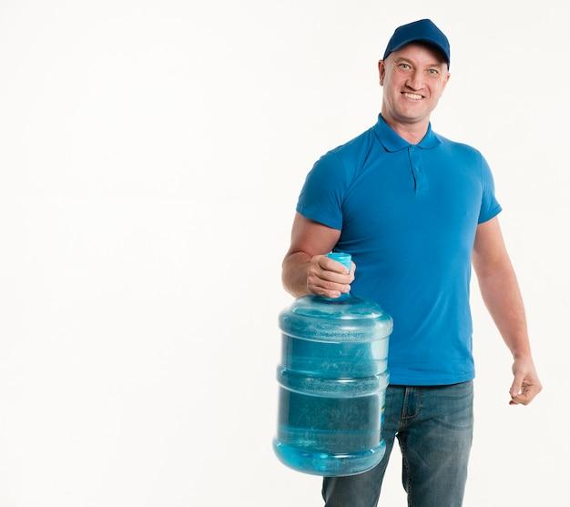 Repartidor sosteniendo la botella de agua y sonriendo