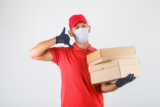 Repartidor sosteniendo cajas de cartón y haciendo señal de llamada en uniforme rojo, máscara médica, guantes vista frontal.