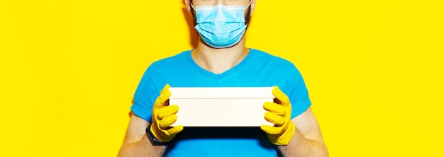 Repartidor sosteniendo una pequeña caja. usar mascarilla médica y guantes de seguridad. color amarillo.