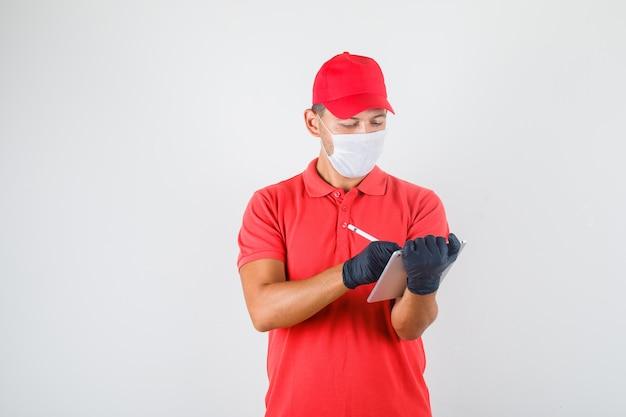 Repartidor tomando notas en tableta con lápiz digital en uniforme rojo