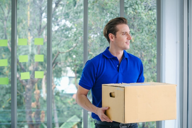 Repartidor en uniforme azul del servicio de entrega, venta en línea, comercio electrónico, concepto de envío.