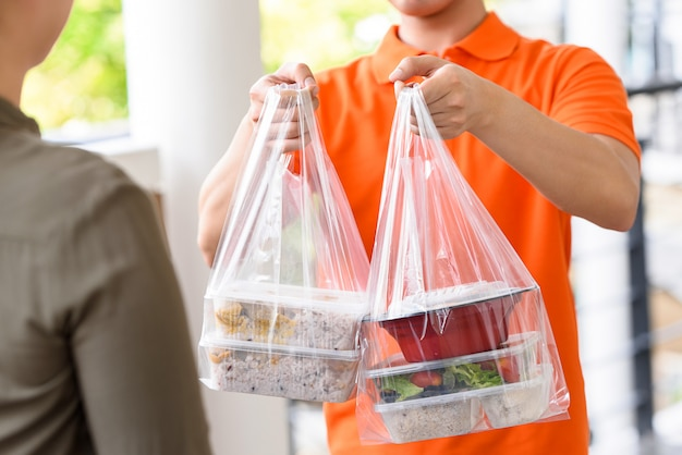 Repartidor en uniforme naranja entregando cajas de comida asiática en bolsas de plástico a una clienta en casa