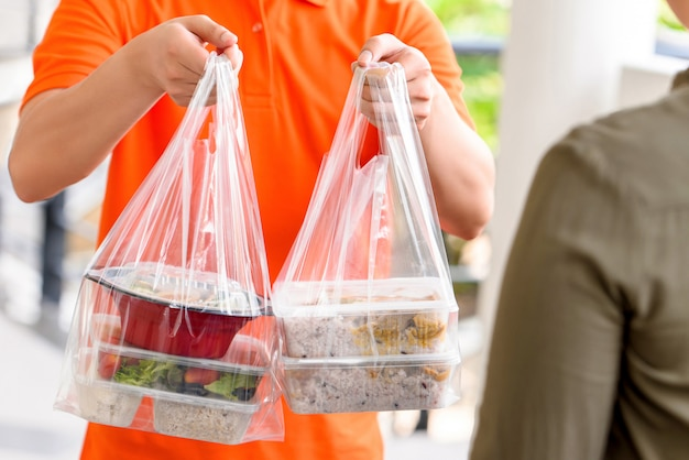 Repartidor en uniforme naranja entregando cajas de comida asiática en bolsas de plástico a un cliente en casa