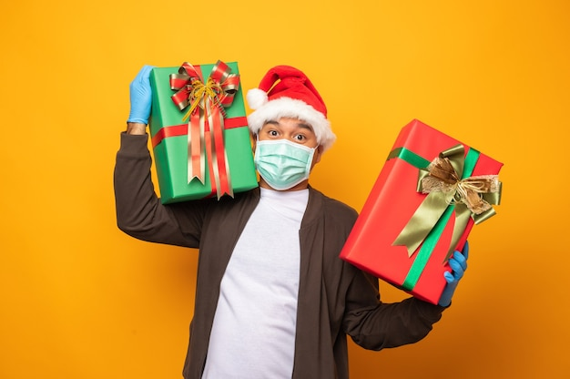 Repartidor en uniforme navideño llevando muchas cajas de regalo