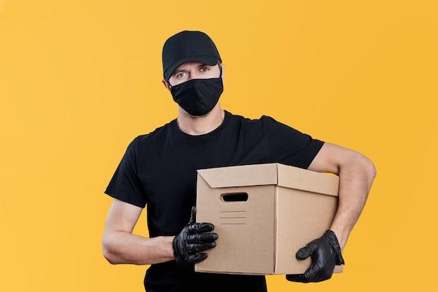 Repartidor en uniforme negro mantenga caja de cartón sobre fondo amarillo. concepto de servicio de entrega sin contacto