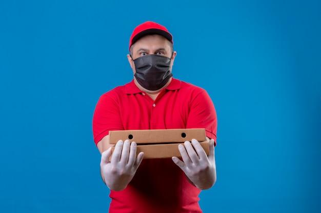 Repartidor con uniforme rojo y gorra en máscara protectora facial con cajas de pizza mirando sorprendido con expresión de miedo sobre la pared azul