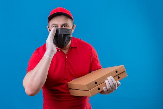 Repartidor con uniforme rojo y gorra en máscara protectora facial sosteniendo cajas de pizza con una mano cerca de la boca contando un secreto sobre la pared azul aislada