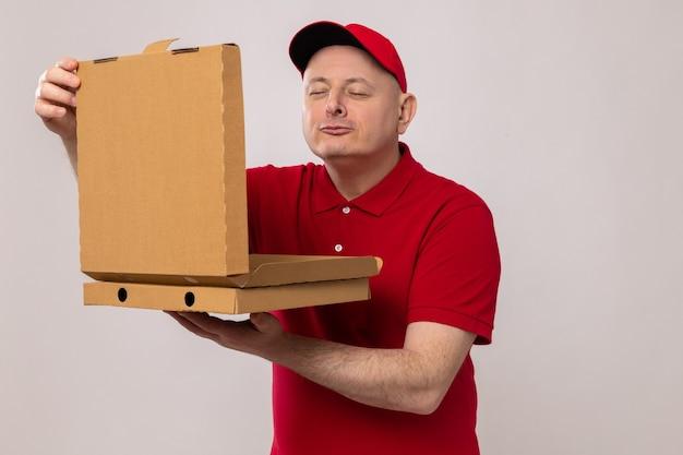 Repartidor en uniforme rojo y gorra sosteniendo cajas de pizza abriendo una de ellas inhalando un aroma agradable
