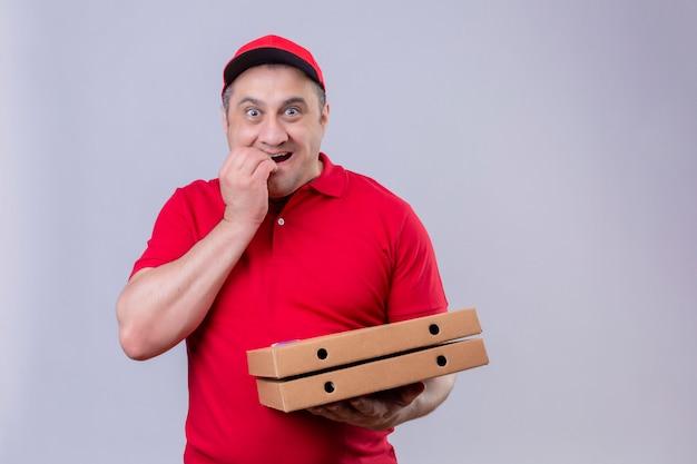 Repartidor en uniforme rojo y gorra sosteniendo cajas de pizza con aspecto estresado y nervioso con la mano en la boca mordiéndose las uñas de pie en blanco