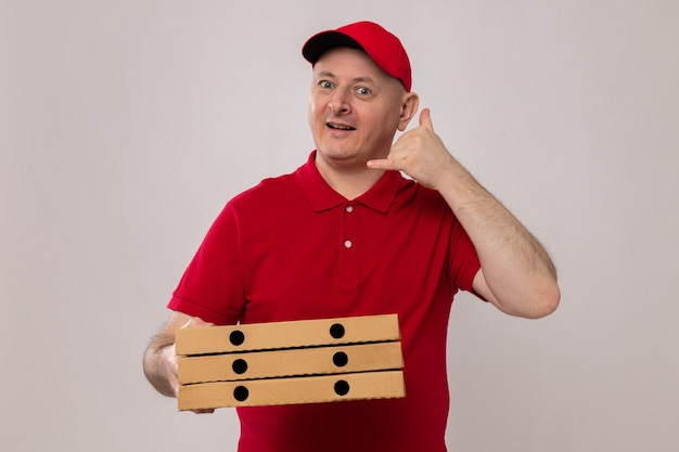 Repartidor en uniforme rojo y gorra sosteniendo cajas de pizza mirando a la cámara sonriendo feliz y positivo haciendo gesto de llamarme de pie sobre fondo blanco
