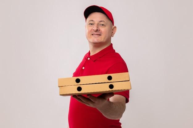 Repartidor en uniforme rojo y gorra sosteniendo cajas de pizza mirando ofreciendo sonriendo alegremente