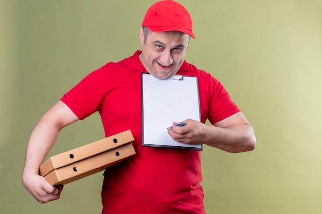 Repartidor en uniforme rojo y gorra sosteniendo cajas de pizza y portapapeles con espacios en blanco pidiendo firma sonriente de pie amistoso en verde