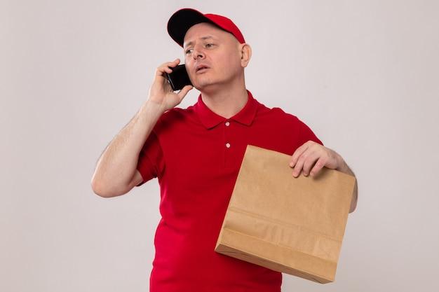 Repartidor en uniforme rojo y gorra sosteniendo el paquete de papel mirando confiado mientras habla por teléfono móvil de pie sobre fondo blanco.