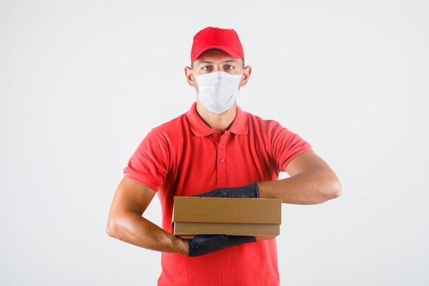 Repartidor en uniforme rojo, máscara médica, guantes con caja de cartón