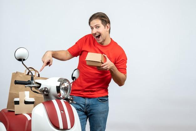 Repartidor en uniforme rojo de pie cerca de scooter mostrando una pequeña caja sobre fondo blanco.