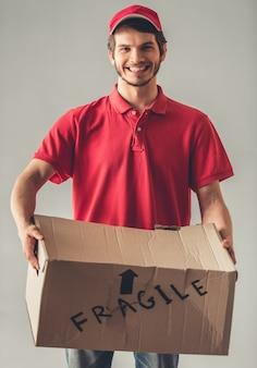 Repartidor en uniforme rojo está sosteniendo una caja de cartón.