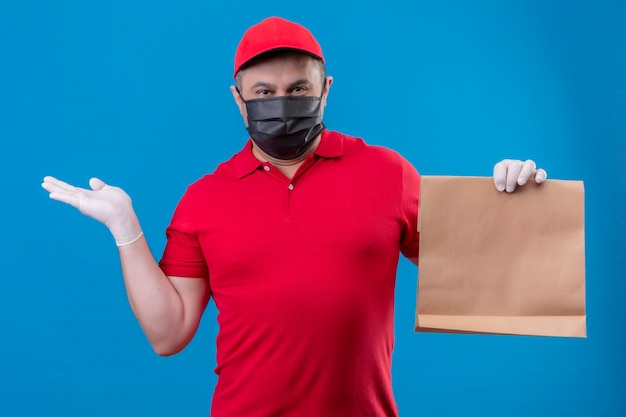Repartidor vestido con uniforme rojo y gorra en máscara protectora facial sosteniendo el paquete de papel que presenta con el brazo oh mano de pie sobre el espacio azul
