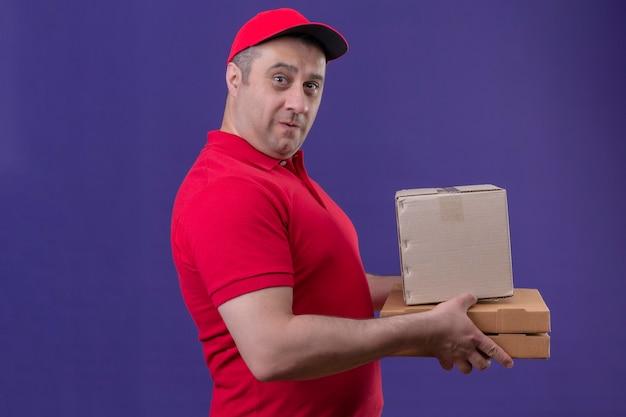 Repartidor vestido con uniforme rojo y gorra sosteniendo cajas de cartón sorprendido de pie