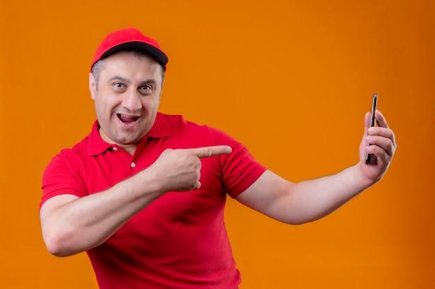 Repartidor vistiendo uniforme rojo y gorra mirando alegre celebración smartphone y señalando con el dedo índice sonriendo sobre la pared naranja