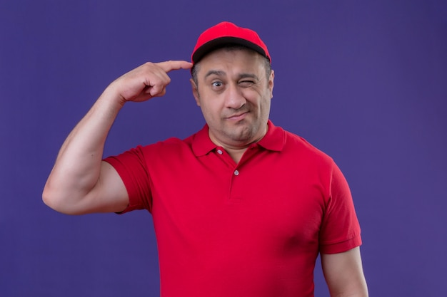 Repartidor vistiendo uniforme rojo y gorra mirando confundido rascándose la cabeza teniendo dudas sobre la pared púrpura aislada
