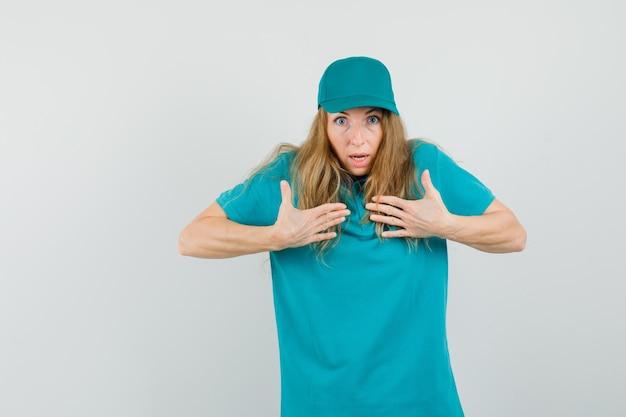 Repartidora en camiseta, gorra apuntando a sí misma para preguntarme y luciendo agitada
