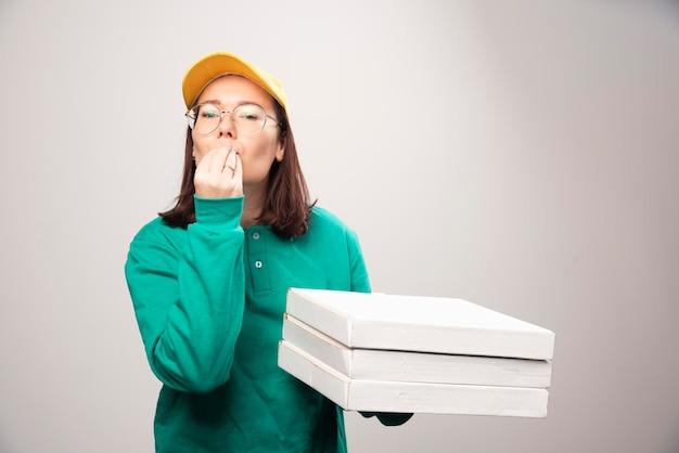 Repartidora llevando cartones de pizza sobre un fondo blanco. foto de alta calidad