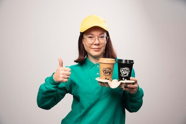 Repartidora mostrando un pulgar hacia arriba y sosteniendo cartón de tazas de café sobre un fondo blanco. foto de alta calidad