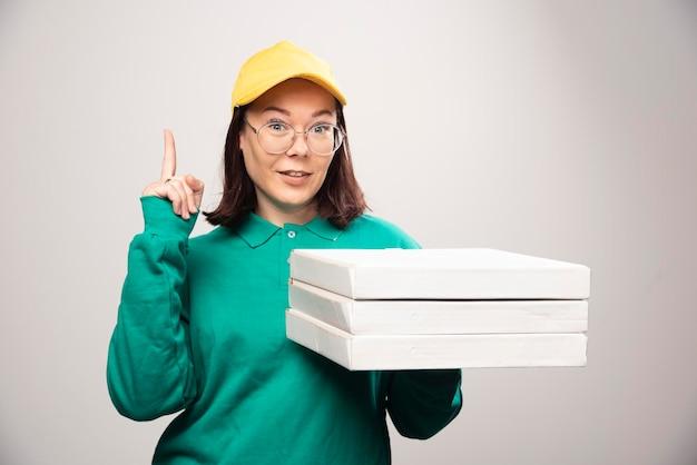 Repartidora mostrando un pulgar hacia arriba y sosteniendo cartones de pizza sobre un fondo blanco. foto de alta calidad