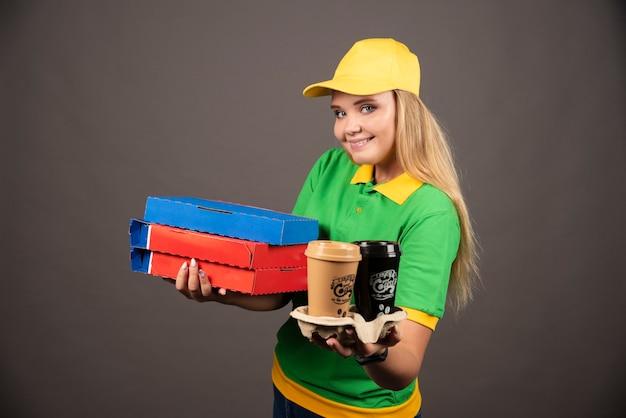 Repartidora ofreciendo tazas de café y cartones de pizza.
