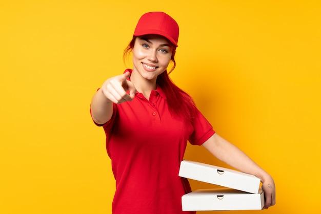 Repartidora de pizza sosteniendo una pizza sobre fondo aislado apuntando al frente con expresión feliz