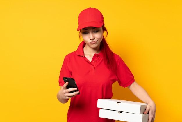 Repartidora de pizza sosteniendo una pizza sobre la pared pensando y enviando un mensaje