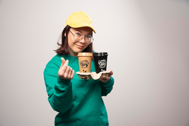 Repartidora sosteniendo cartón de tazas de café sobre un fondo blanco. foto de alta calidad